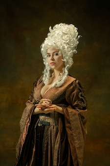 Calm, holding burger. portrait of medieval young woman in brown vintage clothing on dark background. female model as a duchess, royal person. concept of comparison of eras, modern, fashion, beauty.