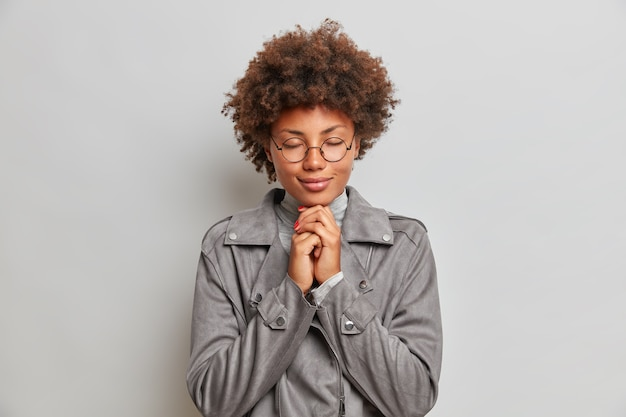 Calm hopeful young woman with curly hair, keeps hands together, prays and hopes for better, enjoys peaceful atmosphere, wears spectacles and grey jacket