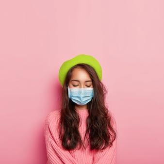 침착 한 여성은 의료용 마스크로 코와 입을 가리고, 전염병이 있으며, 공공 장소에서 보호 마스크를 착용합니다.