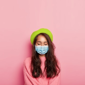 Calm ill woman covers nose and mouth with medical mask, has infectious disease, wears protective mask in public place