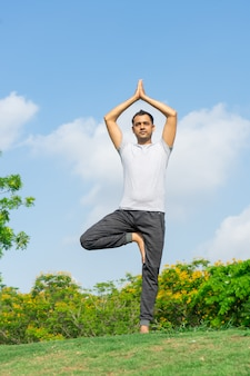 Calm indian man standing in tree yoga pose on summer lawn with bushes