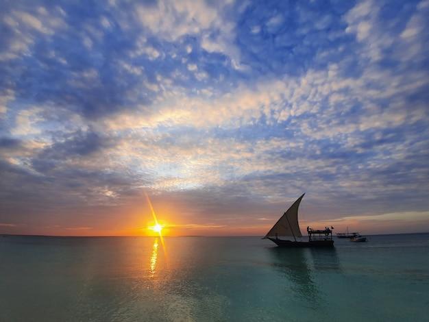 Спокойный индийский океан в лучах заходящего солнца и голубого неба с небольшими облаками. лодка с парусом идет по океану.
