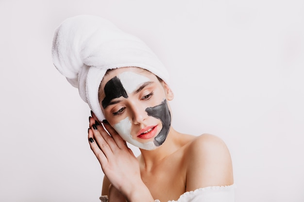 Calm lady in clay mask for face is posing on white wall. portrait of woman doing evening hygiene.