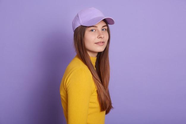 Calm lady dresses casual attire and baseball cap, posing sideways