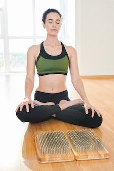 Calm lady meditating at home