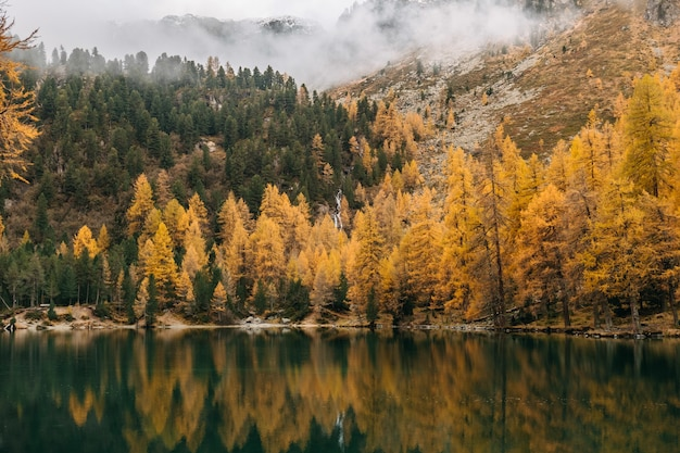 Calm lake and low flying clouds covering a rough mountain covered with colorful autumn foliage