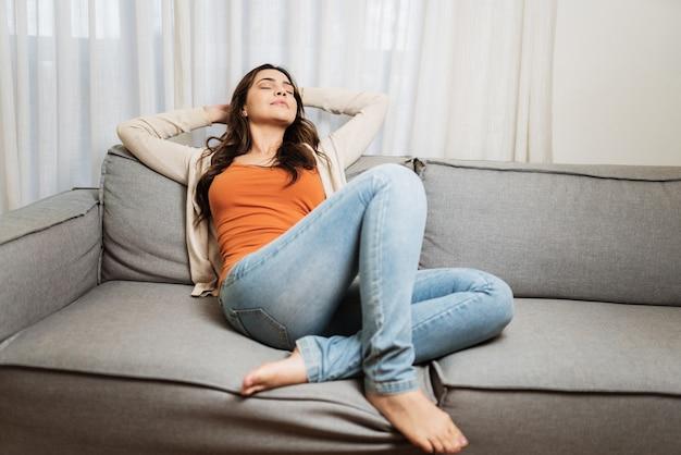 소파에서 스트레스를 받지 않고 부드럽고 편안한 소파에서 휴식을 취하는 차분한 라틴 여성