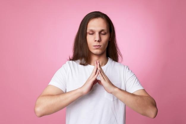 요가 제스처로 손을 잡고 있는 침착한 남자, 편안한 명상, 분홍색 배경에서 진정하려고 노력하는 사람