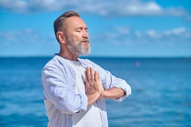 Спокойный мужчина в позе намасте на открытом воздухе