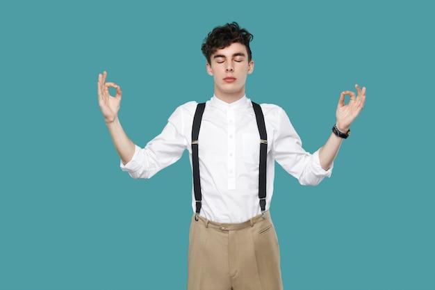 침착한 남자는 요가 손에 팔을 들고 눈을 감았다. 고전적인 캐주얼 흰색 셔츠와 멜빵 서 있는 잘 생긴 힙스터 곱슬머리 젊은 사업가의 초상화. 스튜디오 촬영에 격리 된 파란색 배경입니다.