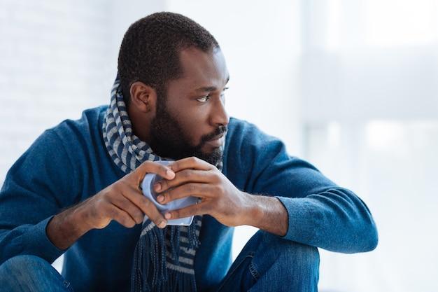 落ち着いた男。お茶を飲みながら静かに座って左側を見る信頼できる厳格な思慮深い男
