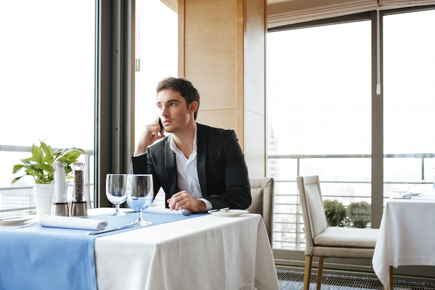 Calm man in restaurant talking on phone