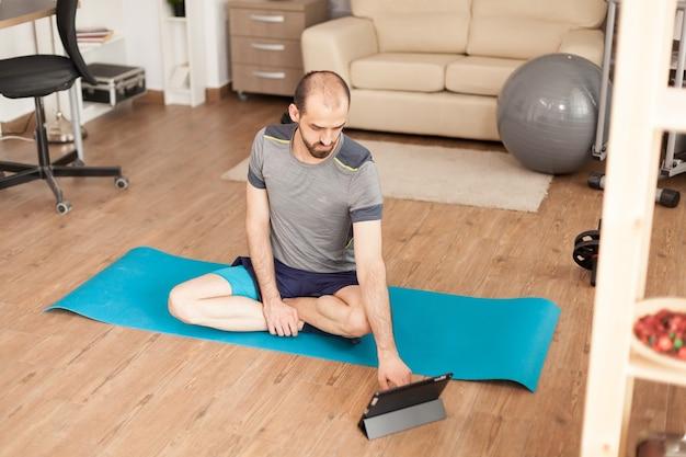Спокойный мужчина смотрит класс йоги на планшетном компьютере во время глобальной пандемии.