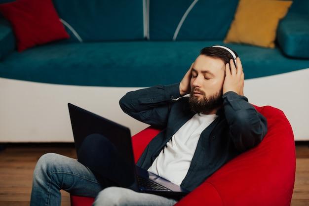 自宅の赤い肘掛け椅子でリラックスしながら音楽を聴きながら目を閉じて穏やかな男。ヘッドフォンで音楽を楽しんでいるハンサムな男。