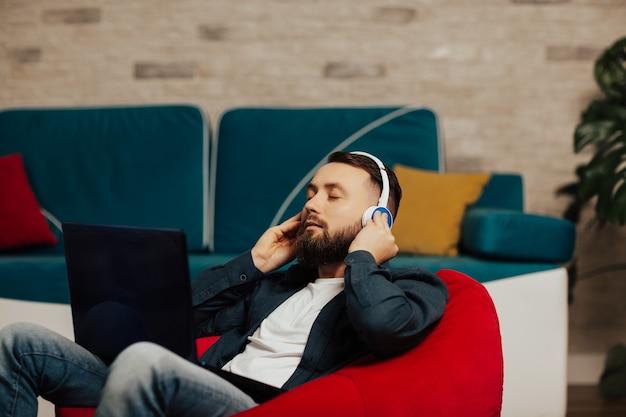 居間の赤い肘掛け椅子に座っている目を閉じた穏やかな男は、ヘッドホンをつけて膝の上にラップトップを持ち、お気に入りのトラックを聴きます。