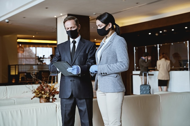 Calm man and woman in fabric masks and rubber gloves looking at the tablet screen in a hotel lobby