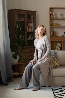 Спокойная зрелая женщина в серой повседневной одежде сидит на краю дивана у окна