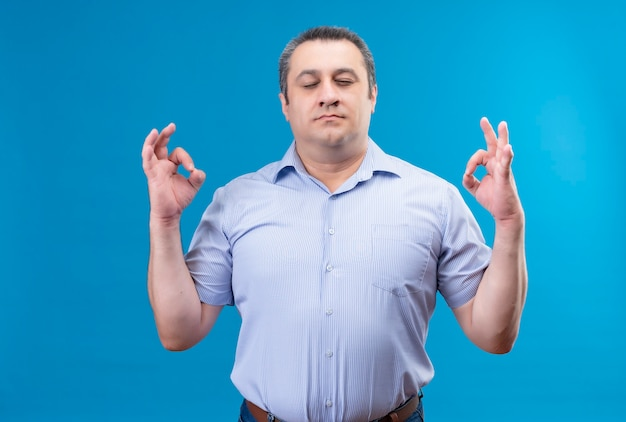 Calm middle age man in blue striped shirt keeping eyes closed making okay gesture with hands on a blue space