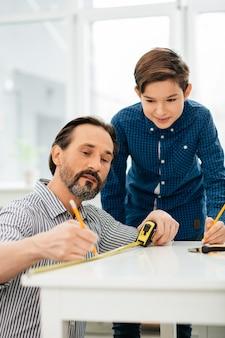 彼の好奇心旺盛な前向きな息子が彼の隣に立っている間、彼の手に巻尺を持って座って線を引く穏やかな中年のひげを生やした男