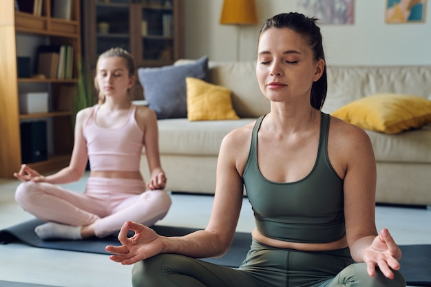 Calm middle-aged mother meditating with closed eyes together with daughter at home