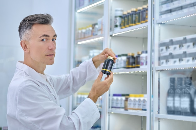 Calm middle-aged pharmaceutist with a sealed plastic medicine bottle standing before the pharmacy display cabinet