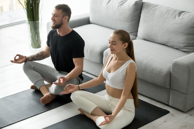 Calm millennial couple meditating in lotus position at home