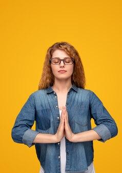 Спокойная современная женщина медитирует с руками вместе