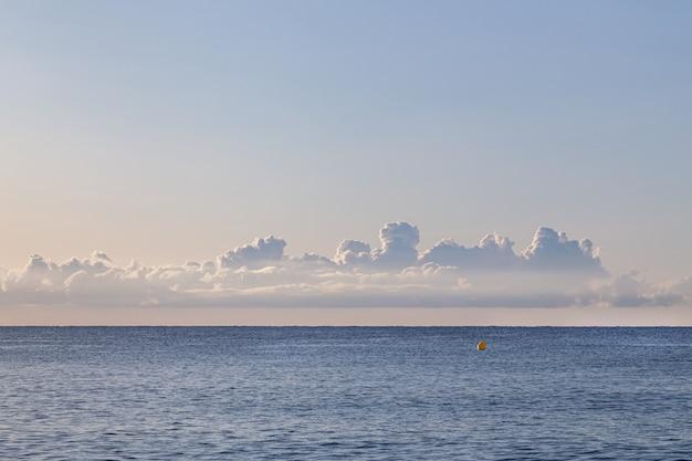 Спокойное утро на пустом пляже с отпечатками автомобильных шин на песке, с морем и облаками на заднем плане