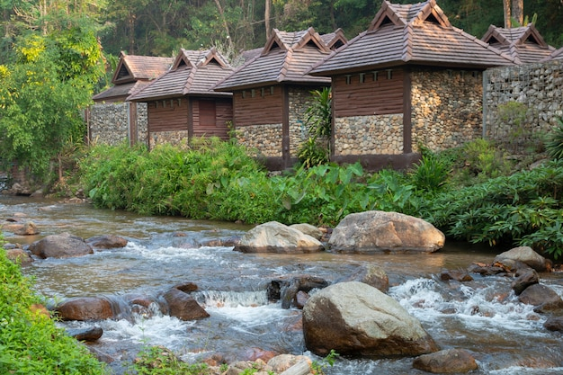 Calm mountain water stream flowing with wooden house.