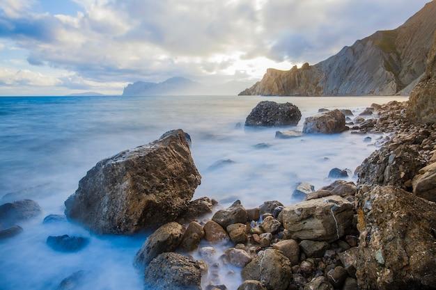 Спокойный океан, покрытый туманом, над ярким небом с облаками. горы вдалеке справа