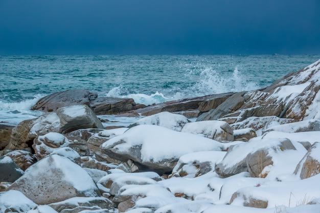 Calm ocean. snow-covered rocky shore. early winter. heavy overcast sky above the horizon