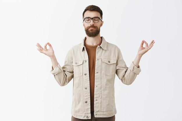 Uomo barbuto paziente calmo in vetri che posano contro il muro bianco