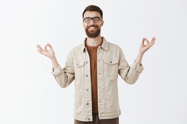Спокойный терпеливый бородатый мужчина в очках позирует у белой стены