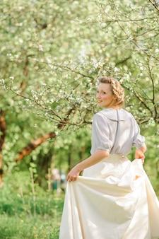 사과 꽃에서 아름 다운 여자의 진정 초상화. 녹지에 현대 꽃 드레스에 boho 소녀 관능적 인 초상화. 텍스트를위한 장소