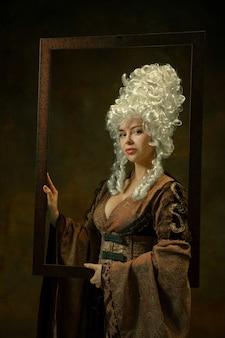 고요한. 어두운 배경에 나무 프레임 빈티지 의류에서 중세 젊은 여자의 초상화. 공작 부인, 왕실 사람으로 여성 모델. 시대, 현대, 패션, 아름다움의 비교 개념.