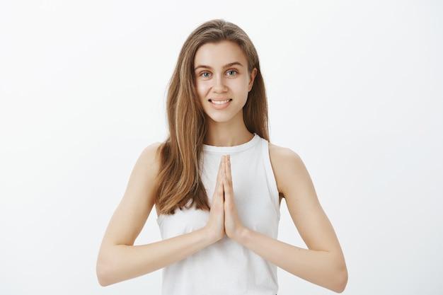 Спокойная красивая девушка медитирует, расслабляется во время йоги, держится за руки в намасте, просит жест