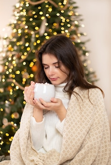 Calm pretty girl sit sofa  have relax in her house with christmas lights  hold mug with hot cocoa or coffee.