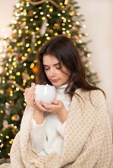 穏やかなかわいい女の子がソファに座って、クリスマスライトがホットココアやコーヒーとマグカップを保持している彼女の家でリラックスしています。