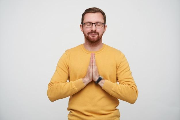 穏やかなかなり若いブルネットのひげを生やした男性は、カジュアルな服装で立って、祈りのジェスチャーで手を組んで目を閉じたまま眼鏡をかけています