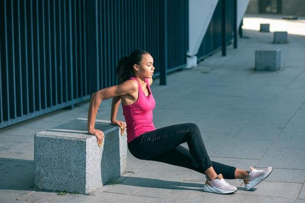 Спокойная профессиональная спортсменка, тренирующаяся в одиночестве на открытом воздухе и выполняющая обратные отжимания на каменном кубе