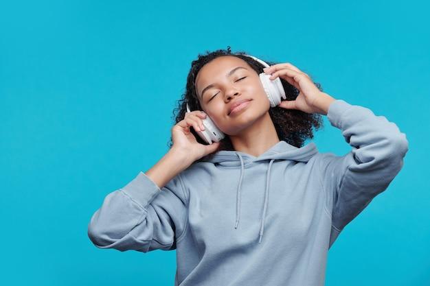 青い背景の音楽を聴きながら目を閉じたままワイヤレスヘッドフォンで落ち着いてリラックスしたアフリカ系アメリカ人の女の子