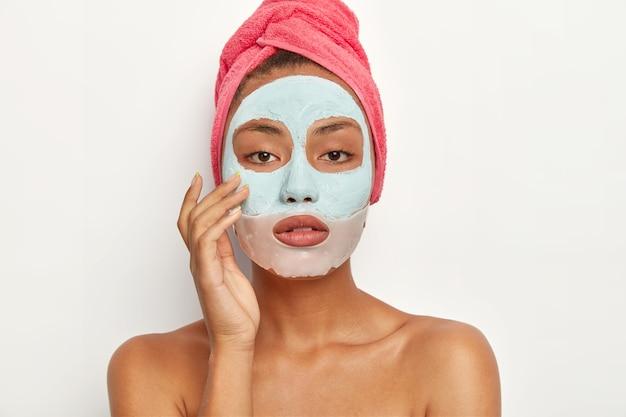 차분하고 편안한 아름다운 여인은 얼굴 점토 마스크를 쓰고 건강과 외모에 관심이 있으며 분홍색의 부드러운 수건을 머리에 쓰고 흰 벽에 알몸으로 서 있습니다. 여성은 얼굴을 정화하고 피부를 정화합니다