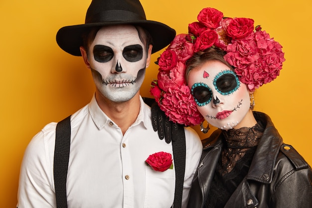 Calm relaxed couple ready for popular carnival, apply spooky makeup, stand with eyes closed against yellow background.