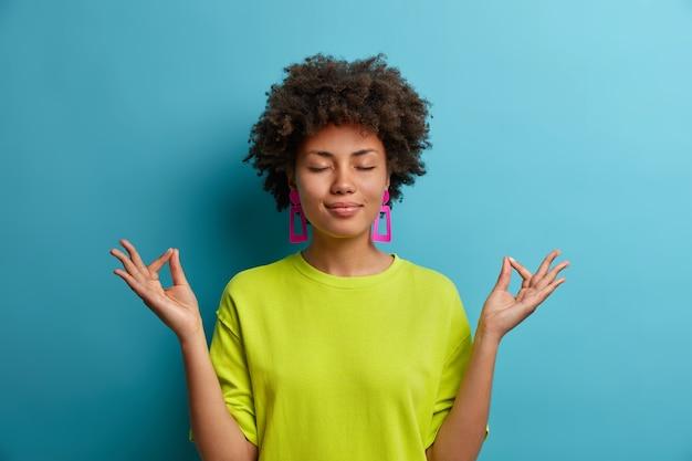 차분하고 편안한 어두운 피부의 여성은 연꽃 자세로 서서 안심하고 평화로운 분위기에 집중하려고 노력하며 캐주얼 한 녹색 옷을 입고 파란색 벽에 고립되어 있습니다. 신체 언어 개념