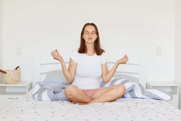 Calm relaxed female with dark hair wearing white casual style t shirt and shorts, sitting on bed in light bedroom in lotus pose, doing yoga practice and meditating.