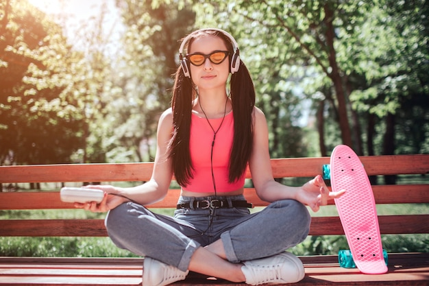 Calm and relaxed girl is meditating. she has crossed her legs and listening to music. girl is doing meditation on bench. there is a pink skate as well.
