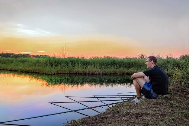 Спокойный расслабленный мужчина много рыбачит, сидя на берегу озера на закате