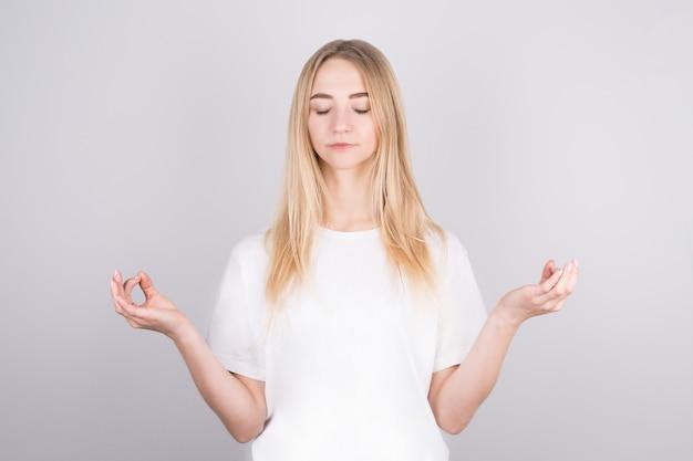 차분하고 편안한 예쁜 금발은 스트레스를 해소하고 눈을 감고 평화롭게 미소 짓고 명상합니다.