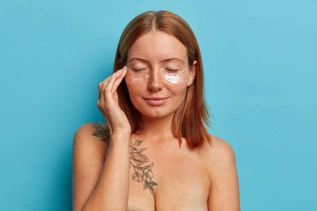 진정 편안한 빨간 머리 여자는 콜라겐 패치를 적용하고, 눈을 감고, 좋은 효과를 기다리고, 주름을 줄이고, 노화 방지 절차를 가지고, 누드로 서 있습니다. 아름다움과 스파 치료 개념