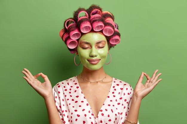 落ち着いたリラックスした女性は、禅のジェスチャーで手を横に広げ、目を閉じたまま、穏やかな雰囲気を楽しみ、緑の壁に隔離されたスキンケアヘアローラーに美容栄養マスクを適用